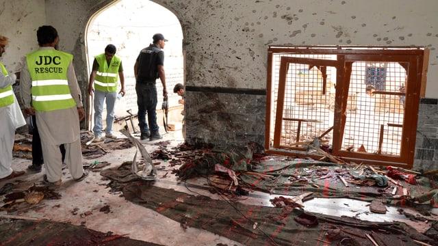 Sicherheitskräfte in einem zerstörten Raum der Moschee