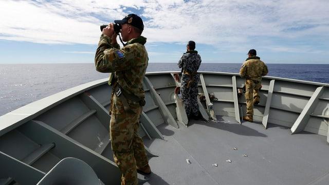 Drei Soldaten blicken vom Bug eines Militärschiffes mit Feldstechern hinaus aufs Meer.