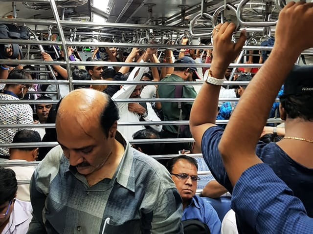 Ein mit Menschen komplett gefüllter Zug von Innen. Viele halten sich fest, einige haben einen Sitzplatz ergattert.