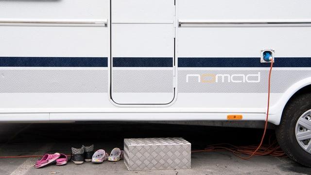 Finken und Schuhe vor einem geschlossenen Wohnwagen.