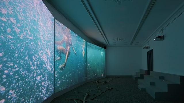 Drei grosse Bildschirme zeigen badende Leute.