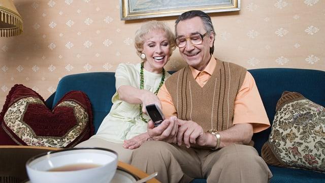 Lachender Rentner mit Handy