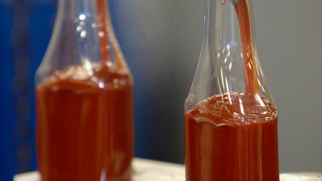 Zwei Heinz-Ketchup-Flaschen in der Abfüllanlage, halb voll.