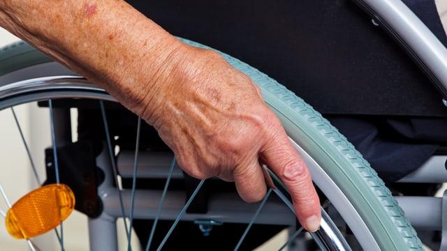 Nahaufnahme Hand an einem Rollstuhl-Rad.