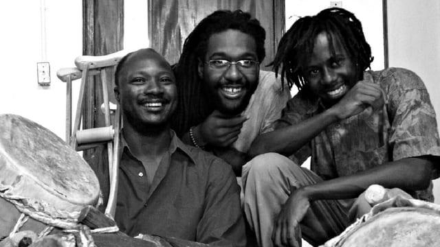 Drei Männer lachen in die Kammera. Am Bildrand sind Trommeln zu sehen.