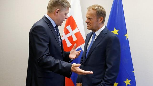 Robert Fico spricht mit Donald Tusk, dahinter Slowakei- und EU-Fahne