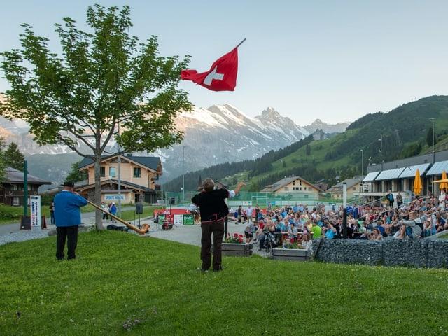 Fahnenschwinger und Alphornbläser unterhalten Touristen.