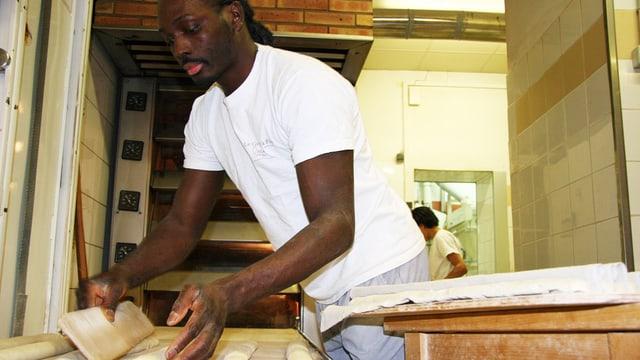 Djibril Bodian formt ein Baguette in seiner Backstube.