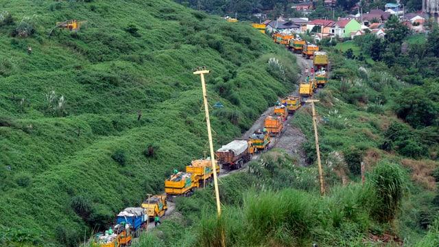 Ein Teil der Abfalldeponie wurde begrünt, während an anderen Stellen Lastwagen immer noch Abfall transportieren