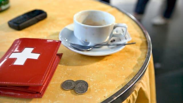 Eine leere Kaffeetasse, daneben Trinkgeld und ein Portemonnaie.
