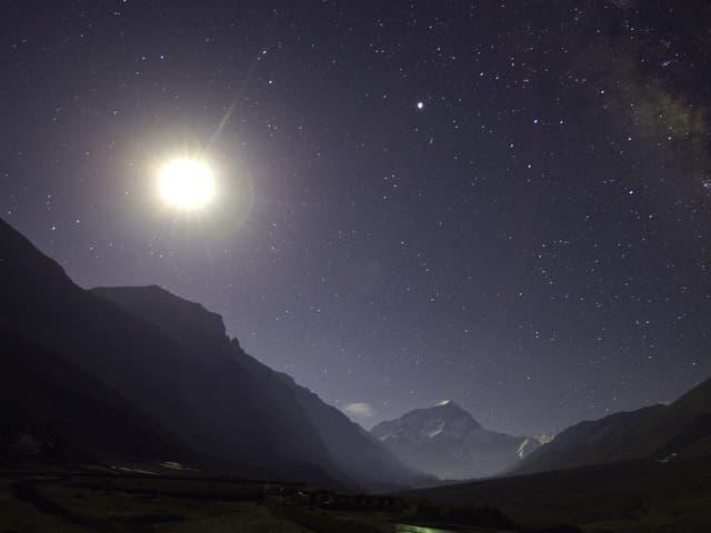 Weit entfernter Gipfel des Mount Everest in der Nacht. Der Mond leuchtet hell.