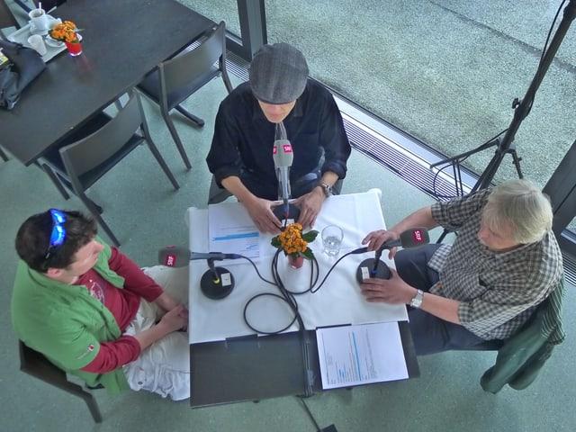 Drei Männer sitzen an einem Tisch mit Mikrophonen. Vor ihnen liegen einige A4-Papiere, auf denen einzelne Passagen mit Leuchtstift angestrichen sind.