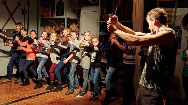 Eine Schulklasse ist auf einer Theatertour im Historischen Museum. Ein Schauspieler zeigt vor, wie Ritter mit dem Schwert kämpfen.