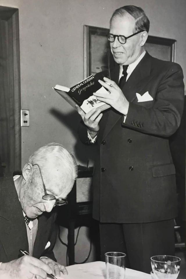 Zwei Männer, einer steht und liest ein Buch. Der andere schreibt etwas.