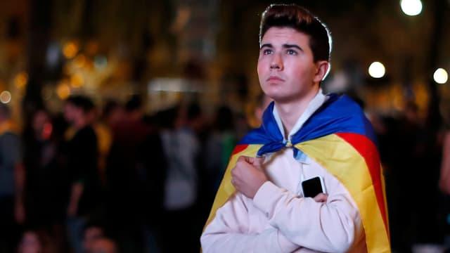 Junger Mann mit katalanischer Fahne über den Schultern.