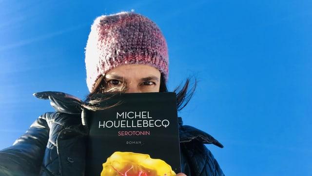 Annette König hält den neuen Roman «Serotonin» von Michel Houellebecq in den Händen. Hinter ihr strahlt der Himmel stahlblau. .