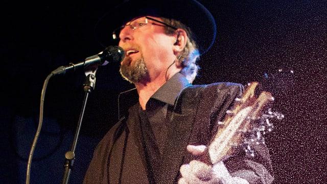 Roger McGuinn am Mikrofon mit Gitarre.