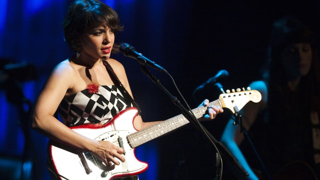 Norah Jones mit Guitarre vor einem Mikrophon auf dem Montreux Jazzfestival.