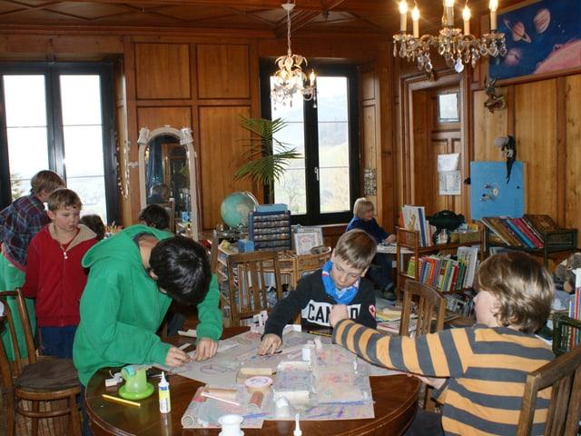 Kinder sitzen in einem Raum an verschiedenen Tischen. Am vorderen wird gebastelt.
