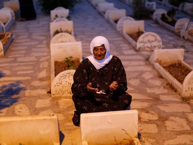 Frau betet am Grab