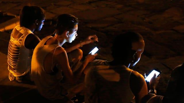 Jugendliche sitzen nachts mit Smartphones am Boden. Ihre Gesichter sind von den Displays beleuchtet.
