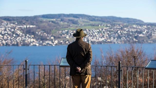 Älterer Mann mit Hut blickt auf den Zürichsee.