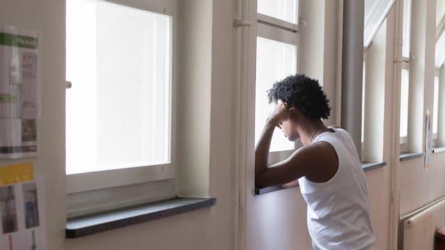 Schwarzafrikaner steht an einem Fenster