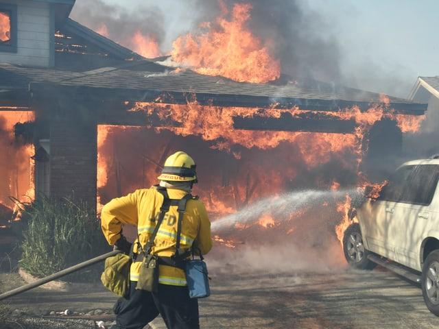 Haus in Flammen, Feuerwehrmann versucht das Feuer zu bekämpfen.