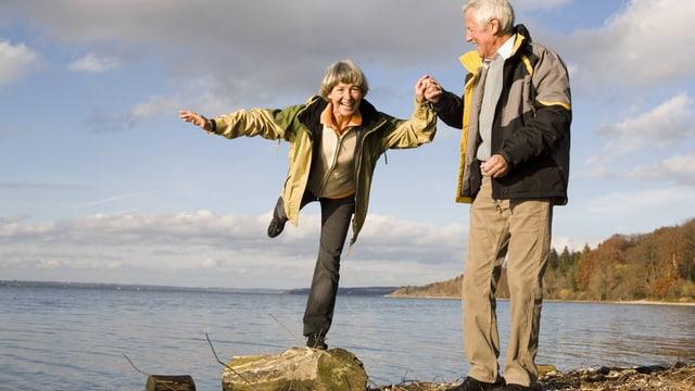 Eine ältere Frau balanciert an der Hand eines älteren Mannes auf einem Stein am See.