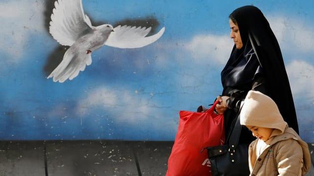 Frau und Kind spazieren vor einer blauen Wand mit weisser Taube