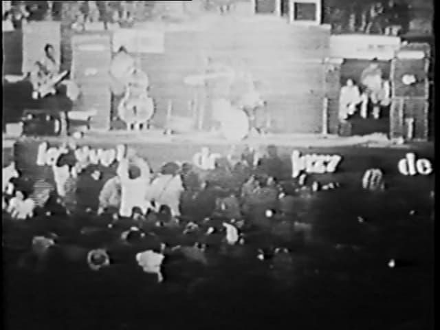 Schwarz-weisses Filmstill, Konzertbühne, Band im Hintergrund, Publikum im Vordergrund