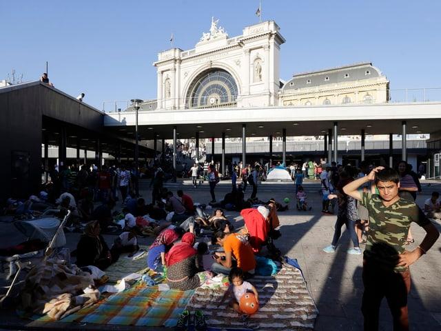 Ein Platz vor dem Bahnhofsgebäude: Familien sitzen auf Decken am Boden, ein Junge (rechts) steht.