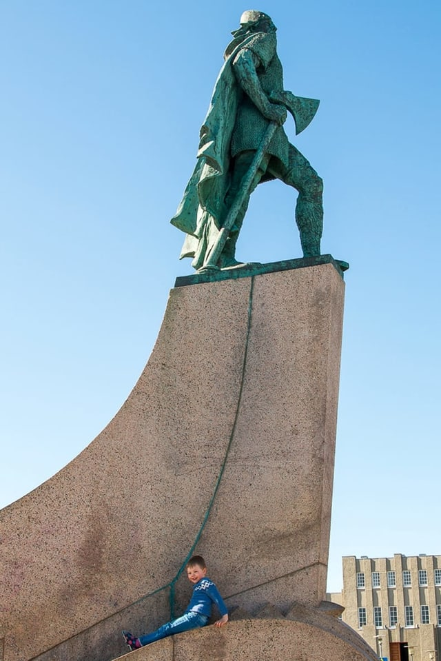 Ein Bub sitzt am Fusse der Statue von Leifur Eiríksson.