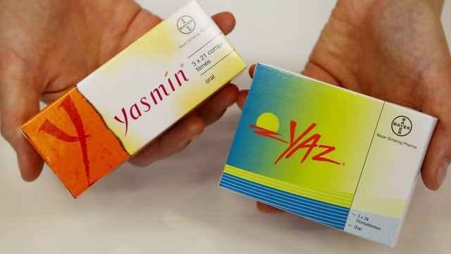 Eine Person hält zwei Medikamentenpackungen in der Hand.