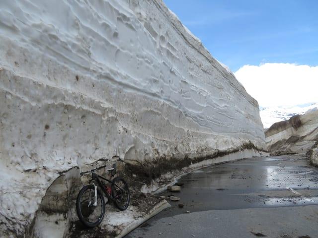 Meterhohe Schneemauer neben der Passstrasse.