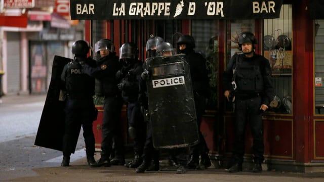 Mehrere Polizisten in Schutzmontur vor einer Bar.
