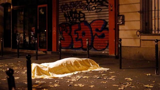 Ein Toter liegt unter einem Leintuch auf der Strasse.
