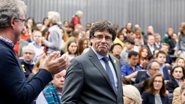 Puigdemont steht inmitten von sitzenden Zuhörenden. Einer von ihnen steht und klatscht dem Separatistenführer zu.