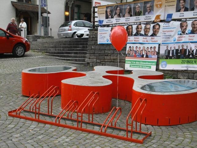 Roter Veloständer vor Wahlplakaten
