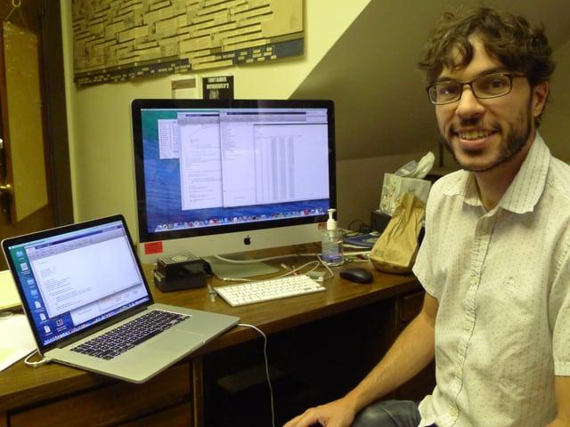 George Mohler, ein Mann mit dunklen Locken und Brille, an seinem Schreibtisch, auf dem ein Apple-Computer und ein Laptop stehen.