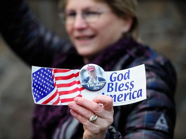 Frau mit Trump-Button und Wahlwerbung in der Hand.