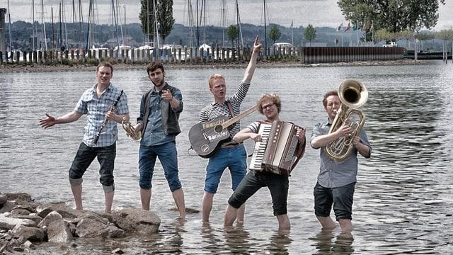 Die fünf jungen Musiker stehen mit kurzen Hosen im Wasser am Ufer eines Sees.