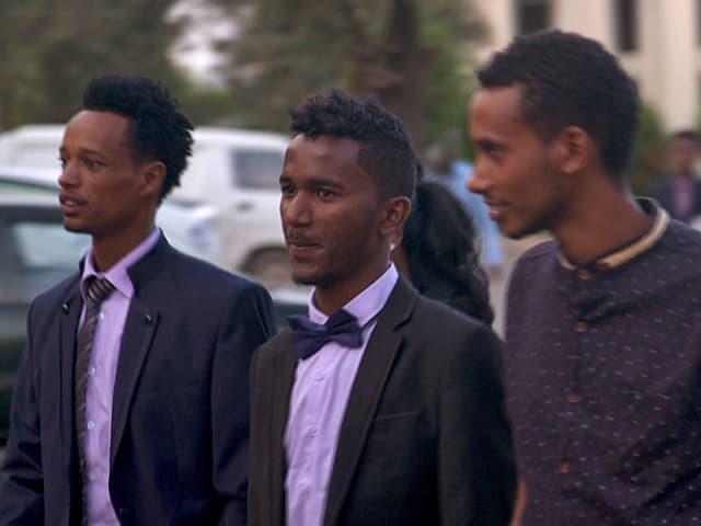Drei Studenten in Anzügen.