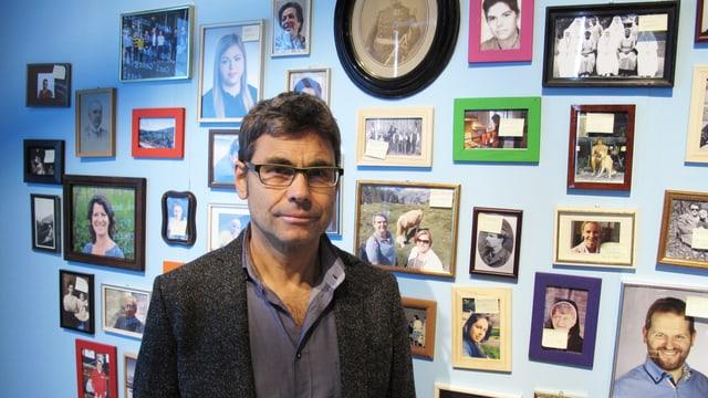 Mann steht vor einer Wand mit unzähligen aufgehängten gerahmten Bildern.