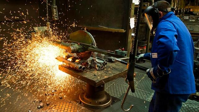 Arbeiter, der Gusseisen verarbeitet. Es sprühen Funken.