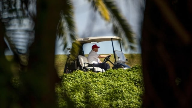 Trump im Golfcaddy, fotografiert aus der Ferne.