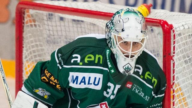 Goalie mit weissem Helm und grünem Dress.