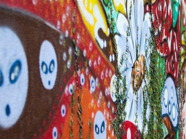 Farbenfrohe Blumen sind an einer Wand gezeichnet.
