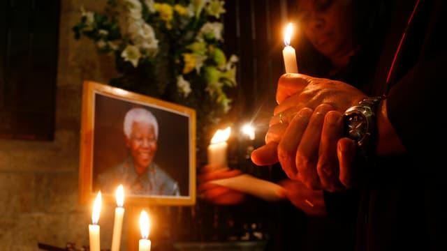 Zwei Menschen mit Kerzen in stiller Andacht vor einem Portrait des lächelnden Mandelas.