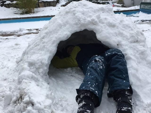 Schneehütte mit Kind darin.